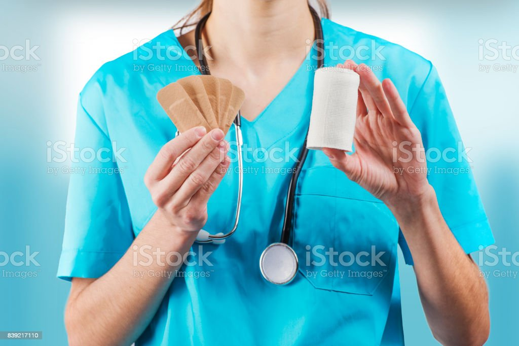 woman nurse or doctor hands closeup while presenting first aid items, bandage and patches stock photo