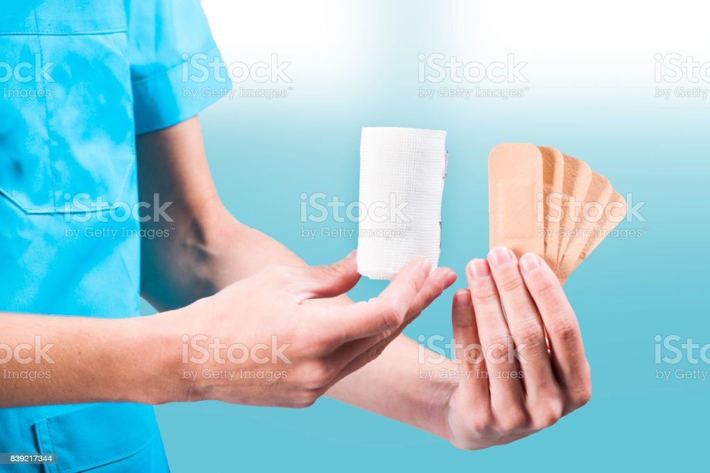 woman nurse or doctor hands while presenting first aid items, bandage and patches stock photo