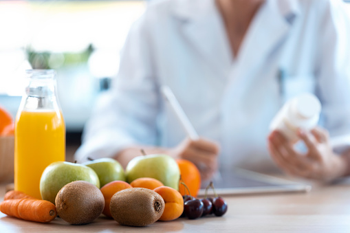 Close-up of woman nutritionist doctor writes the medical prescription for a correct diet on a desk with fruits, pills and supplements.
