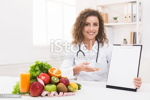 Effective dieting menu and slimming program. Woman nutritionist pointing on blank clipboard at office