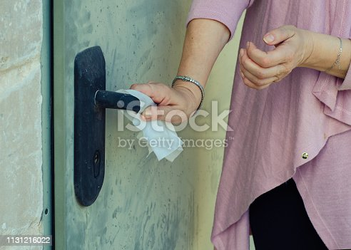 Before pressing the handle a woman sanitized it with the hygiene towel. She suffers from mysophobia.