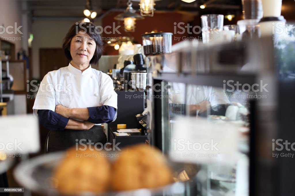 Woman of an elderly person running the cafe stock photo