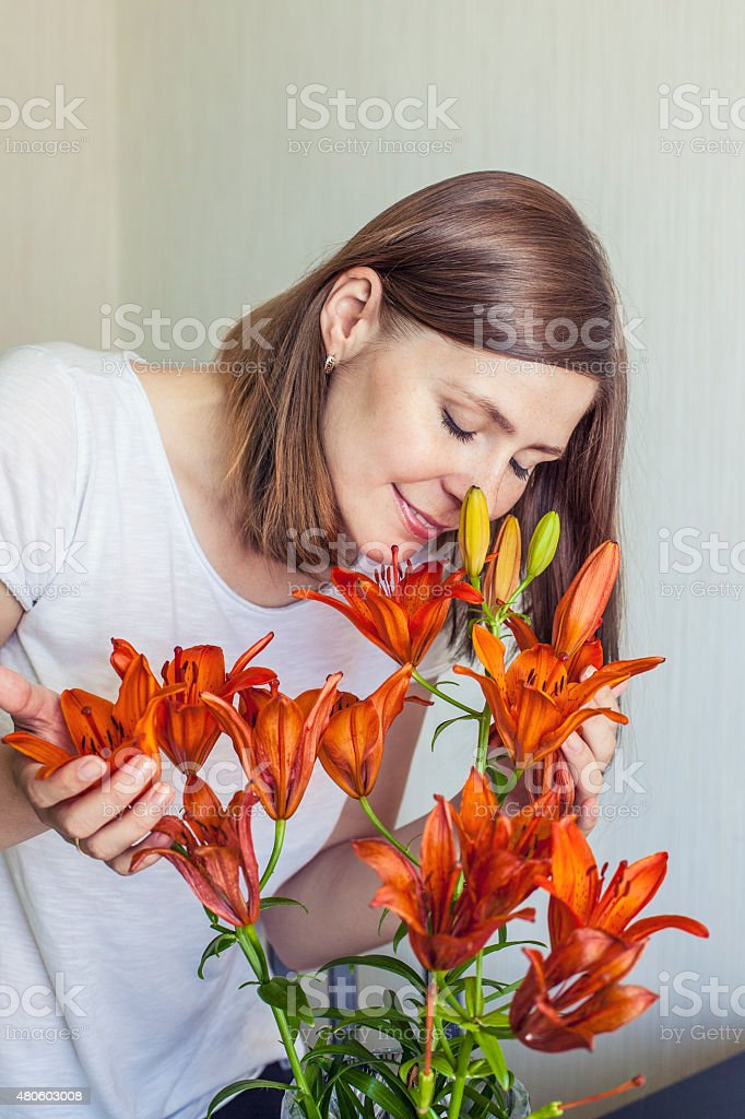 Woman of the house inhales the scent of orange lilies royalty-free stock photo