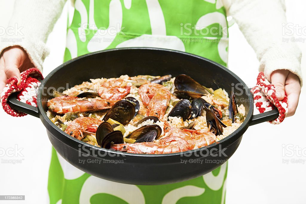 Woman offering an spanish paella royalty-free stock photo
