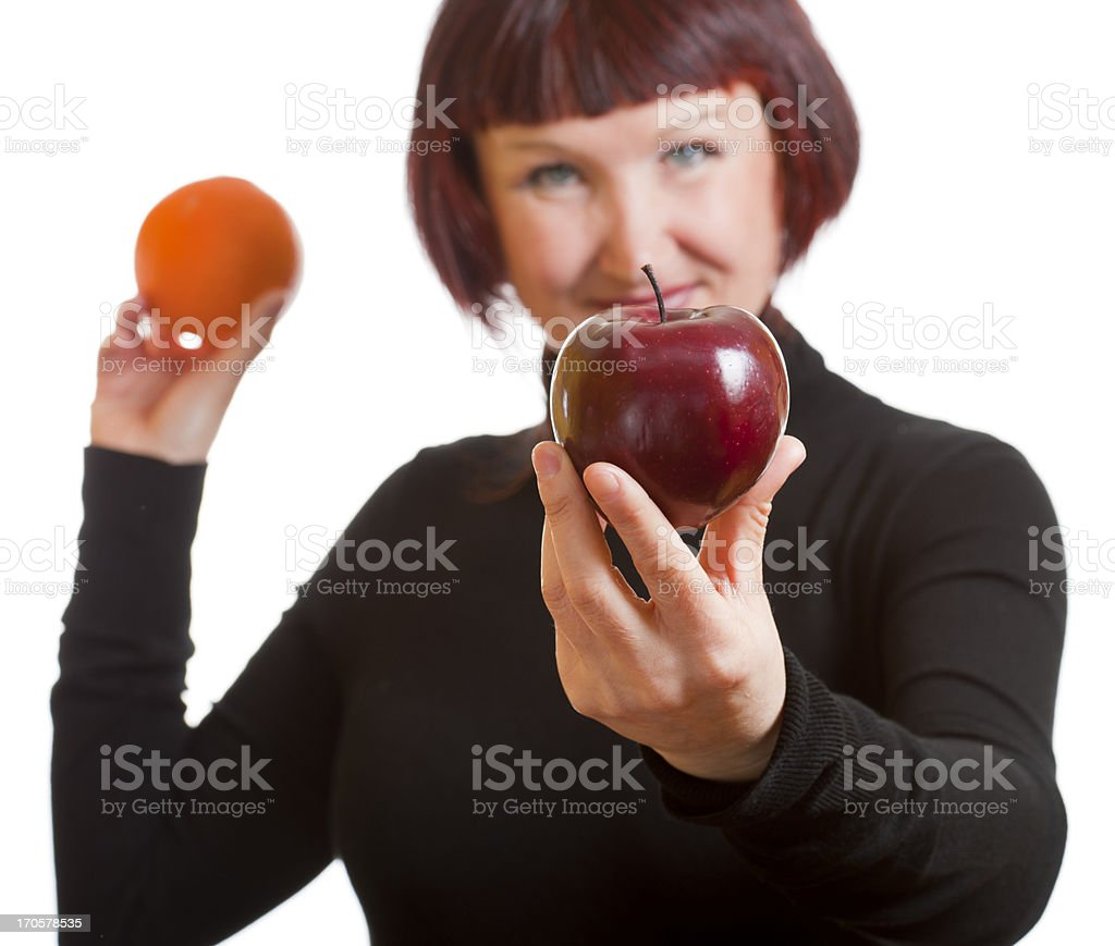 Woman Offering Choice of Red Apple or Orange stock photo