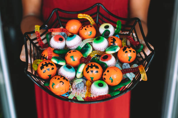 Woman offering funny Haloween candy at the front door stock photo