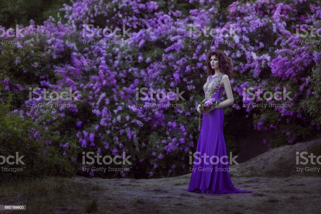 Woman on a background of blooming lilac flowers. stock photo