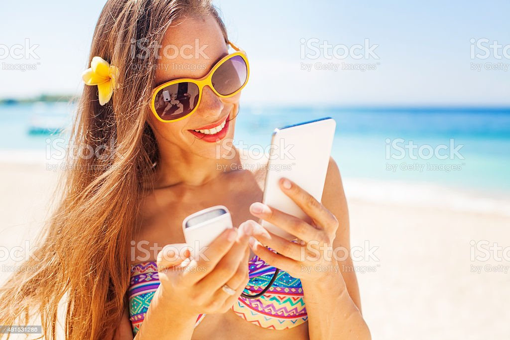 woman on a beach holding a phone in her hands stock photo