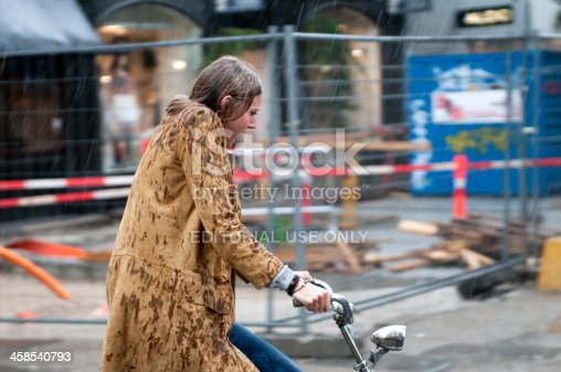 Copenhagen, Denmark - June 17th, 2011: Woman rides a bike as heavy rain come pouring down.  Her hair and jacket gets soaked.