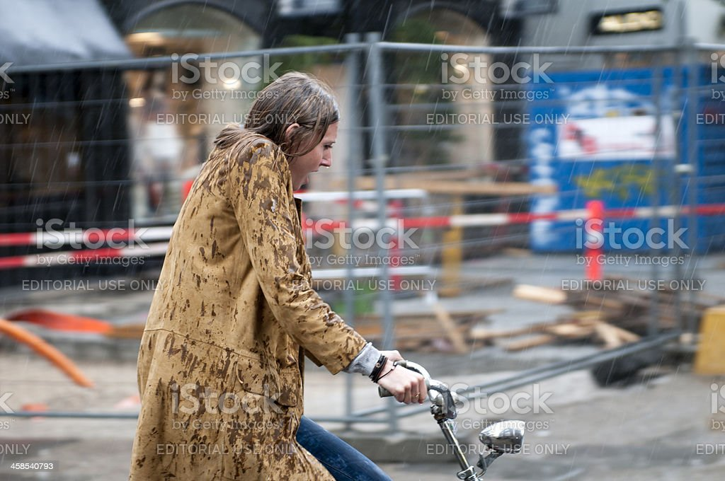 Woman on a bicycle in pouring rain stock photo