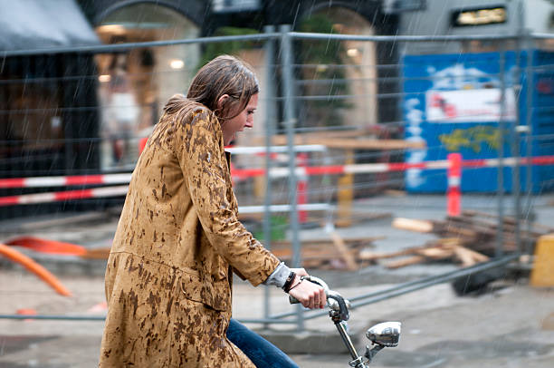 woman on a bicycle in pouring rain - drenched stock pictures, royalty-free photos & images