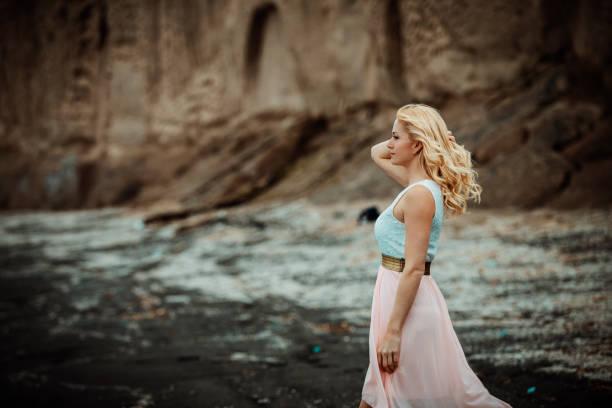 Frau an einem schwarzen Sandstrand auf Santorin, – Foto