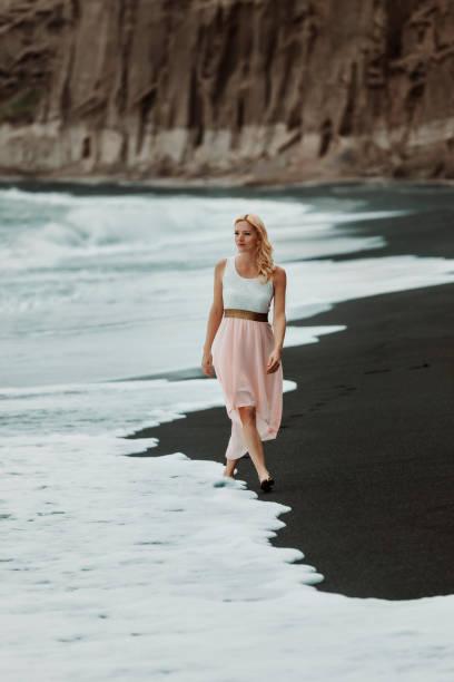 woman on a black sand beach on Santorini, stock photo