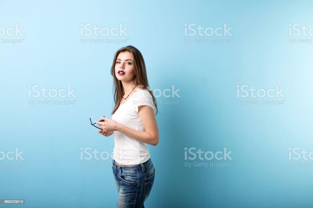 Woman on a blue wall background. ロイヤリティフリーストックフォト