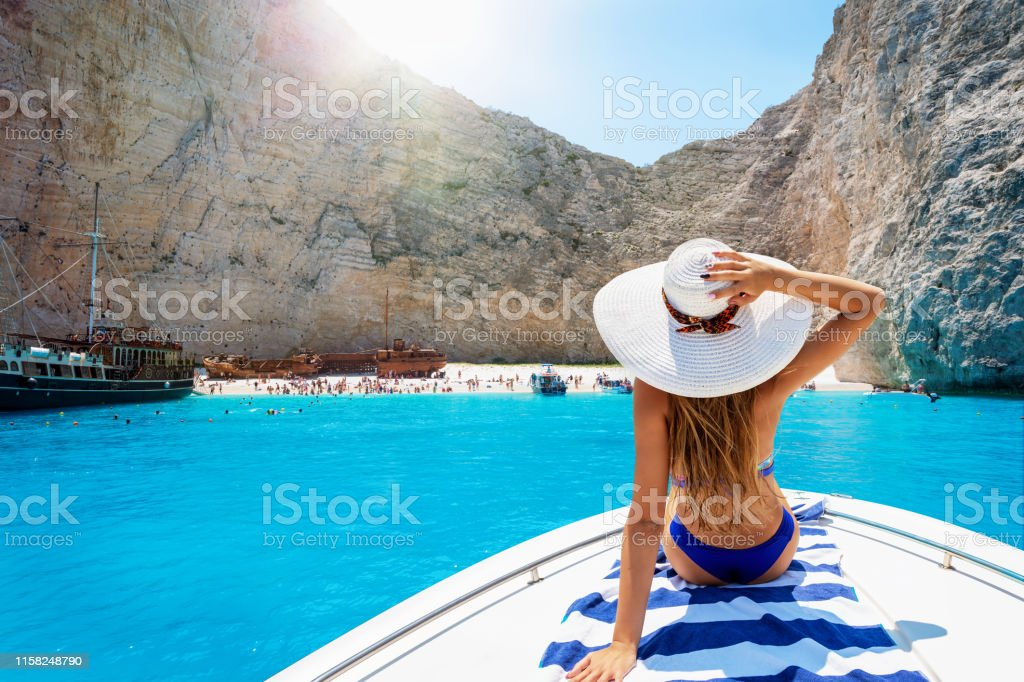 Woman on a boat enjoys the view to the shipwreck beach, Navagio in Zakynthos, Greece Beautiful, blonde woman in a bikini on a boat enjoys the view to the famous shipwreck beach, Navagio, in the island of Zakynthos, Greece Adult Stock Photo