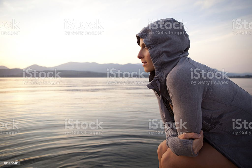 Woman on a boat gazing at the lake during sunset stock photo