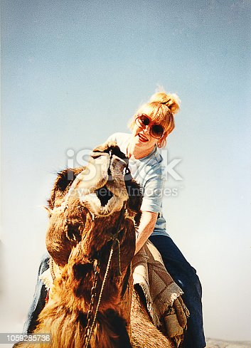 Image of a woman mounting on a camel against a blue sky.
