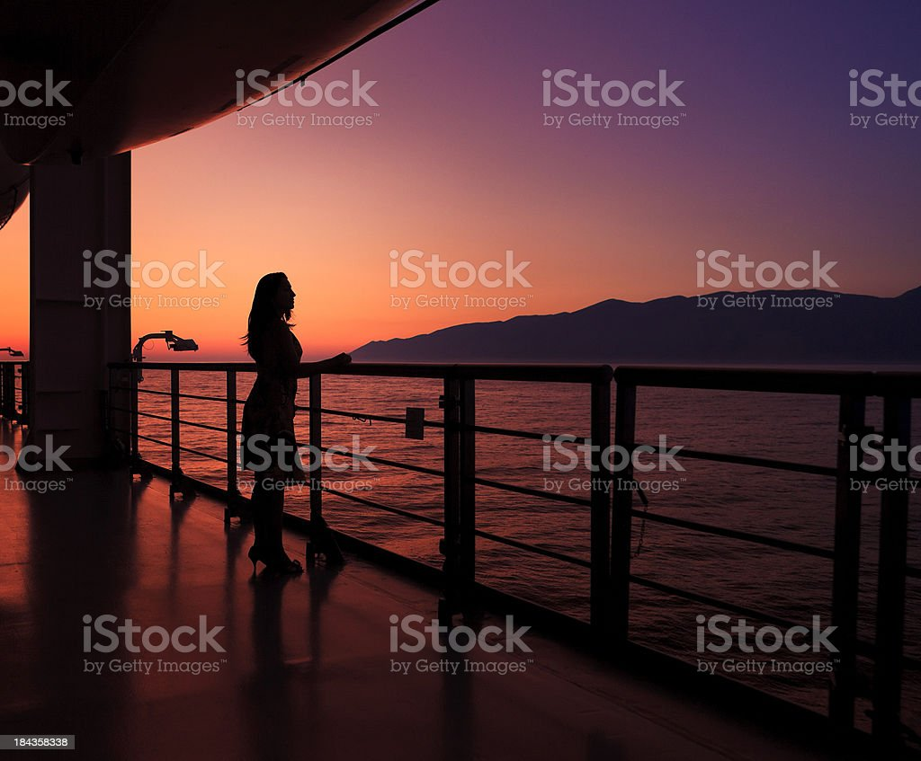 woman on a cruise ship at sunset stock photo