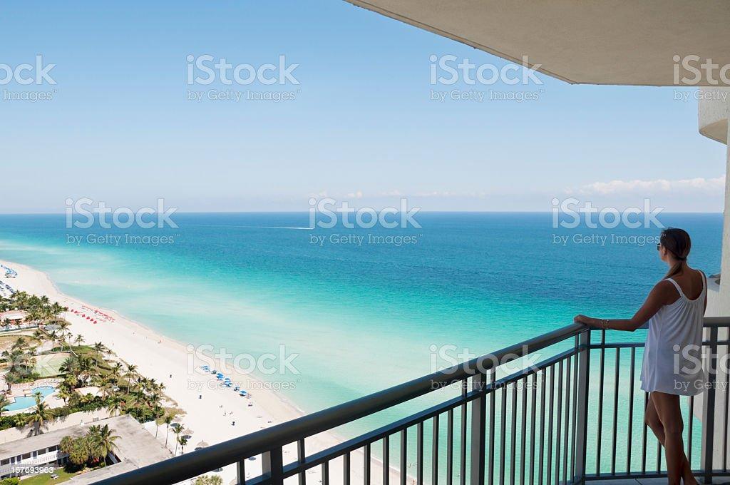 Mujer en un gran balcón con vista a la playa tropical de Miami - foto de stock