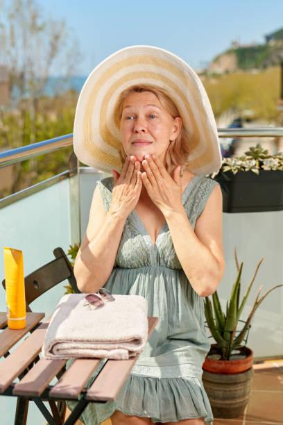 Mujer en la terraza de un hotel junto al mar. Mujer aplicando crema solar en hombro bronceado. Protección solar. Cuidado de la piel y el cuerpo - foto de stock