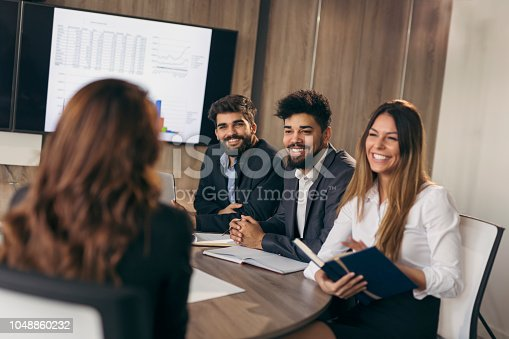 Business woman on a job interview with three human resources representatives as a board members. Focus on the man in the middle