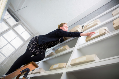 istock Woman on a ladder reaching for a box out of reach 169940116