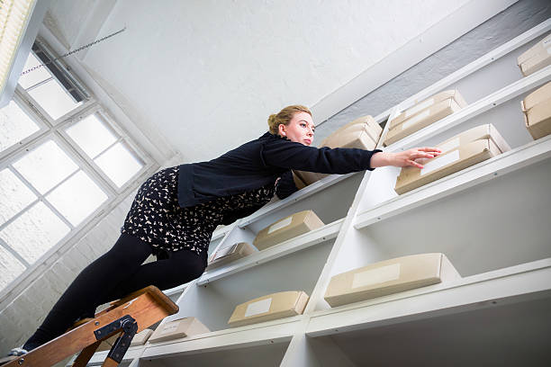 woman on a ladder reaching for a box out of reach - danger stock pictures, royalty-free photos & images