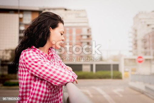 A young and attractive girl looks ahead against the background of the street. Retro style.