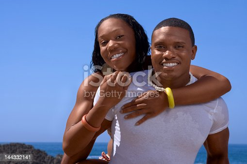 istock A woman on a mans back smiling for the camera 144332141