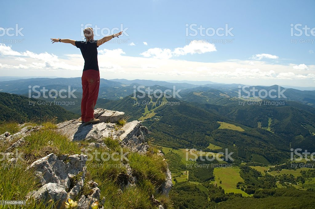 Woman on a mountain peak with outstretched arms stock photo