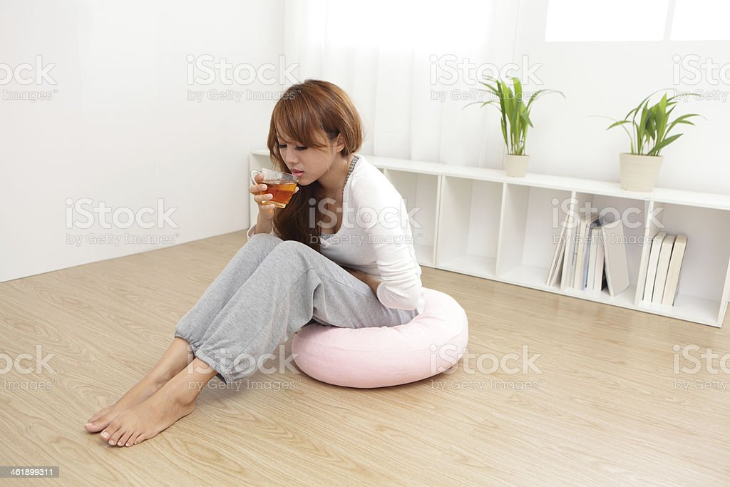 A woman on a pink cushion holding her stomach and drinking royalty-free stock photo