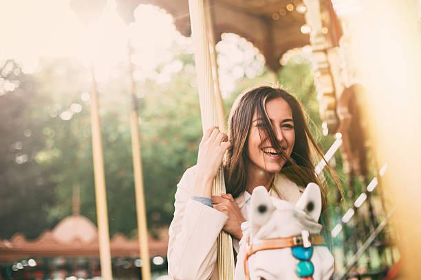 woman on a roundabout - karussell stock-fotos und bilder