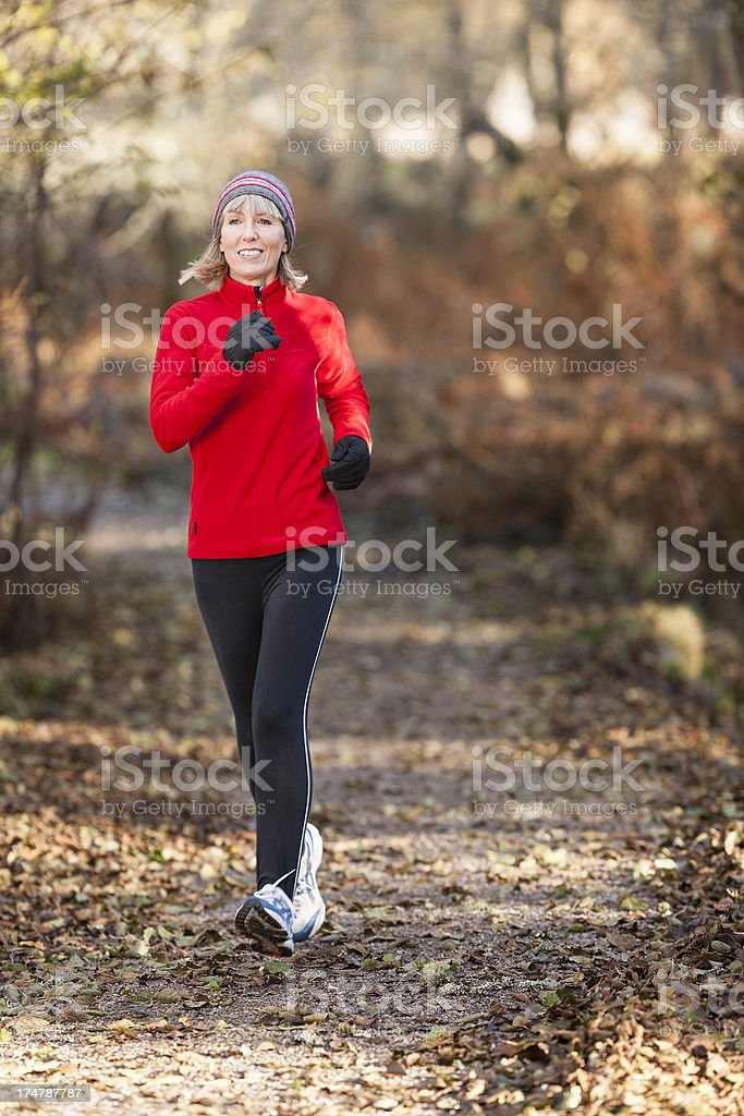 Woman on a run through a forest stock photo
