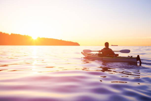Woman on a sea kayak is paddling in the ocean