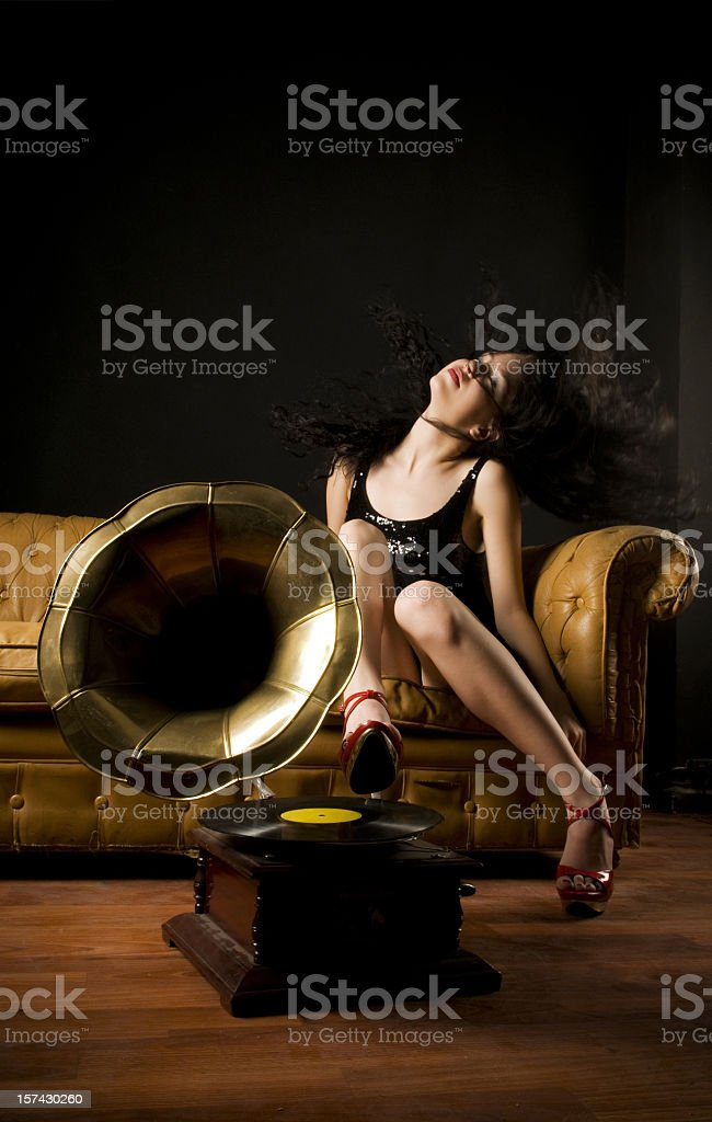 Woman on a sofa swishing her hair in front of a gramophone stock photo