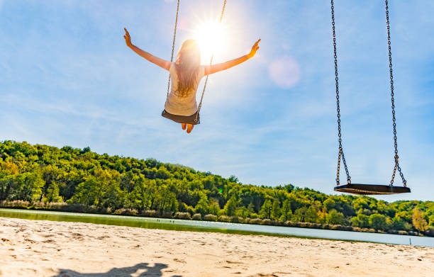 Woman on a swing at a lake Woman on a swing at a lake with sandy beach sun shining through dresses stock pictures, royalty-free photos & images