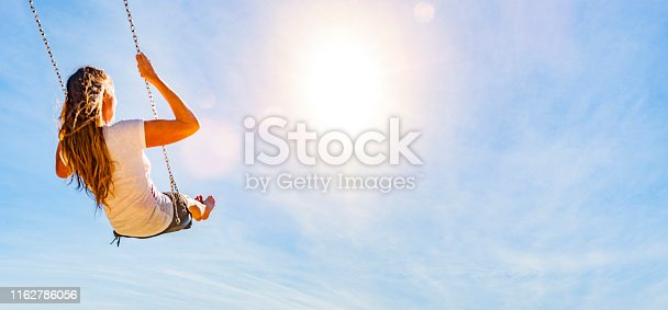 istock Woman on a swing with blue sky 1162786056