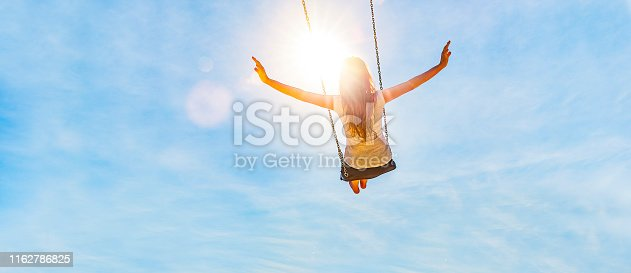 Woman on a swing with blue sky in the back light