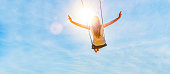 istock Woman on a swing with blue sky 1162786825