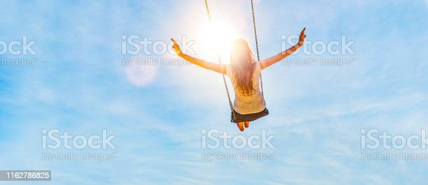 Photo of Woman on a swing with blue sky