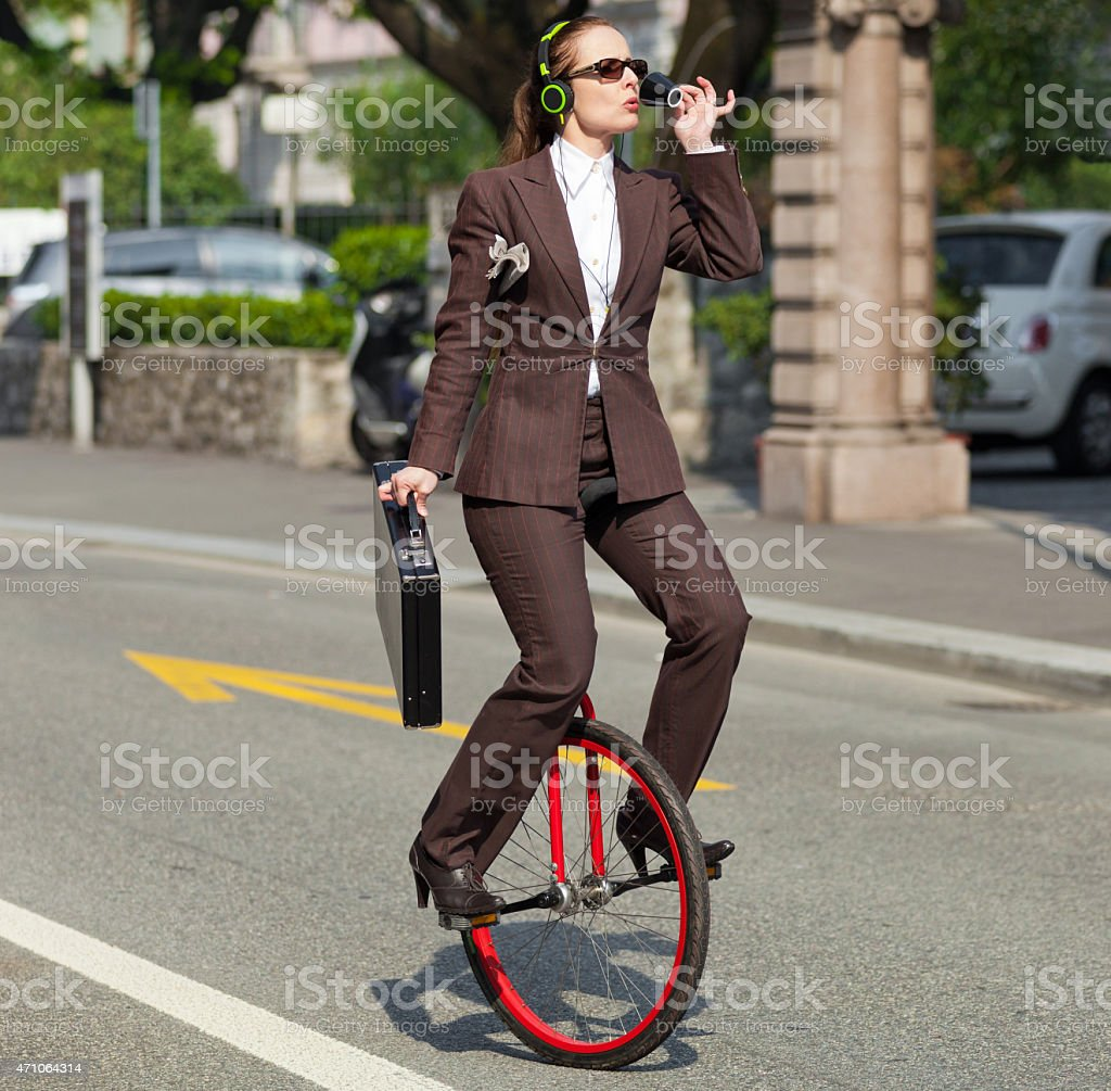 Woman on a unicycle holding a briefcase and on the phone stock photo