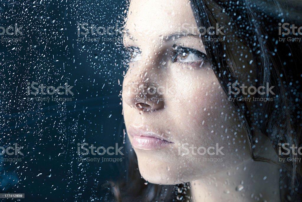 Woman On A Window In The Rain stock photo
