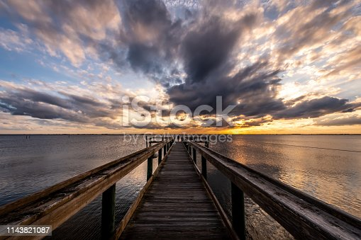 One woman looking at a cloudy sky during sunset on a wooden wharf over Banana river situated on the east coast of Florida.