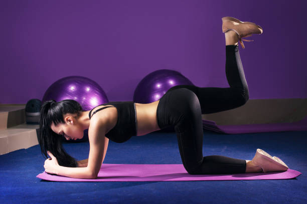 woman on abdominals workout posture in gym . plank bent leg raise - peso mosca foto e immagini stock