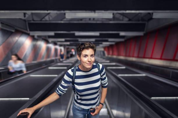 Woman on an escalator at a subway station stock photo