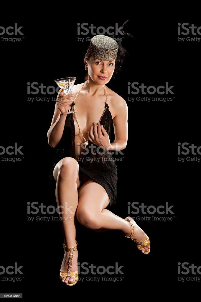 Donna in poltrona con un bicchiere di cocktail foto stock royalty-free