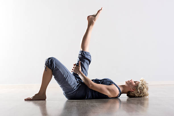 Woman on back stretching hamstring muscles Single athletic woman with blond hair in blue outfit on back stretching hamstring muscles for leg in mid air hamstring stock pictures, royalty-free photos & images