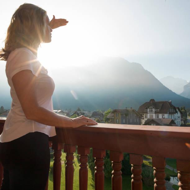 frau auf balkon hält hand zum sonnenlicht, schweizer alpen - hotel bern stock-fotos und bilder