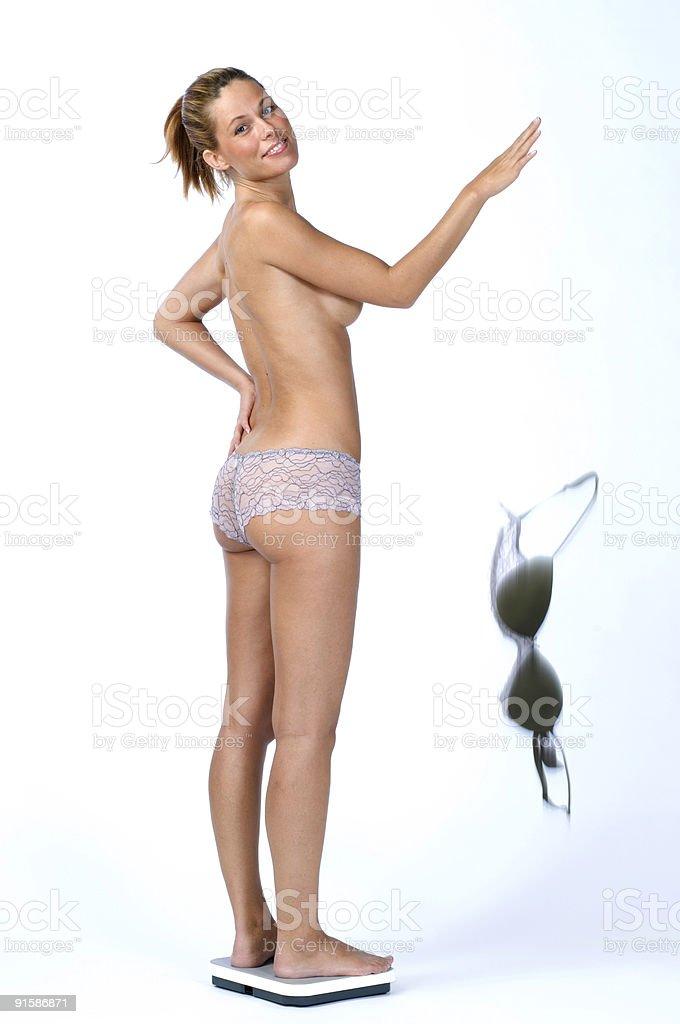 woman on bathroom scale dropping bra stock photo