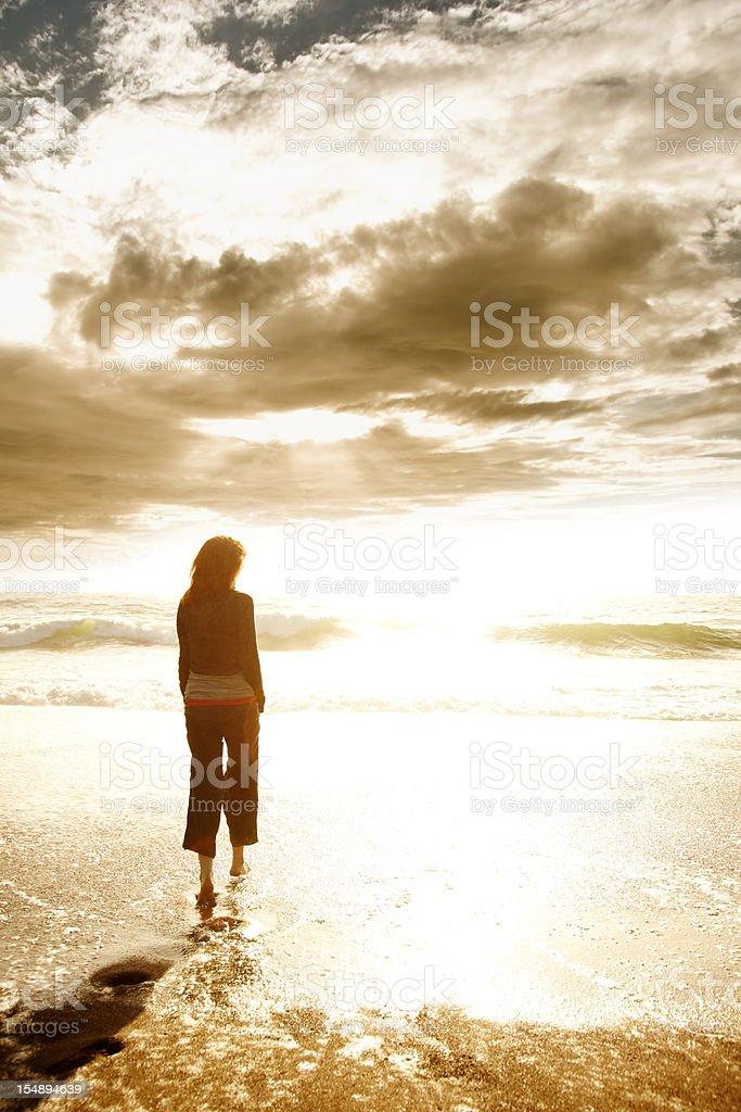 Woman on beach at sunset stock photo